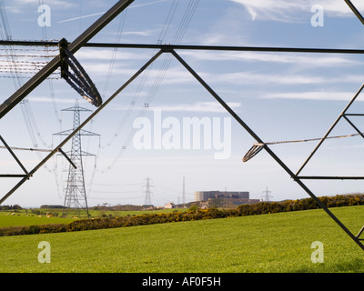 Power lines from Wylfa A Nuclear Power Station seen through metal struts of an electricity pylon Cemaes Anglesey - Stock Photo