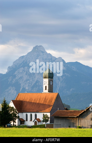 classic architecture of small Bavarian church and alps of Allgau region in early morning, Speiden, Germany - Stock Photo