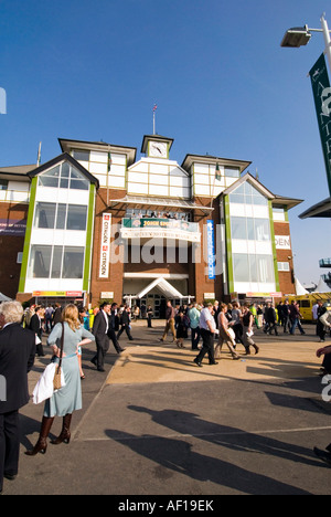 Crowd walking by Queen Mother stand on sunny day at Aintree race course, Liverpool - Stock Photo