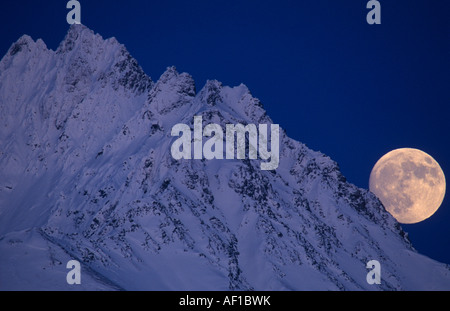 USA Alaska Chugach National Forest Full moon rises over snow covered Chugach Range above Knik River - Stock Photo