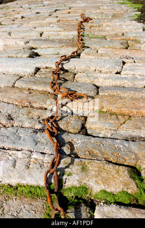 abandoned chains on rocks of pier  - Stock Photo