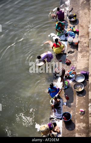 Women washing clothing on steps of Ramkund bathing tank, Nasik, Maharashtra, India - Stock Photo