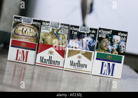 packages of  cigarettes with pictures of dead people, ill, cancer - Stock Photo