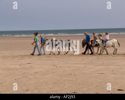 BENLLECH ANGLESEY NORTH WALES UK July Two young children having a donkey ride across the beach - Stock Photo