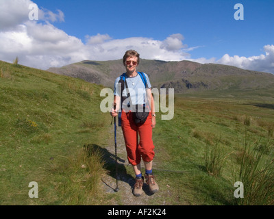 SNOWDON Ranger Path  GWYNEDD UK August Fit Woman walking down along Snowdon Ranger path from Snowdon in the background - Stock Photo