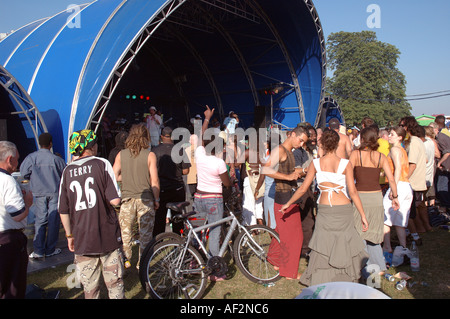 Young people dancing drinking and celebrating at festival in Brockwell Park South London. - Stock Photo