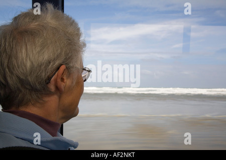 Woman tourist sat looking out through coach window traveling on Ninety Mile Beach with rough sea Aupori Peninsula - Stock Photo