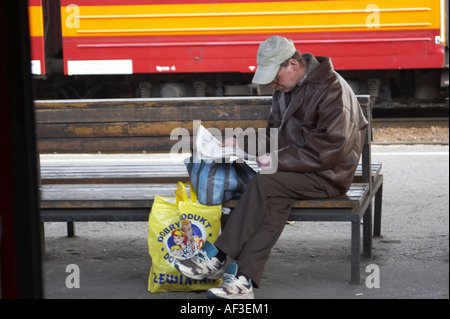 Upper Silesia Poland. Man sitting on  a bench reading newspaper - Stock Photo