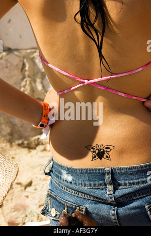 Tattoo painting artist at work on young woman arms akimbo on mexican beach resort - Stock Photo