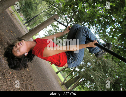 attractive korean Asian woman hanging upside down on bar in park in Clapham, South London, UK - Stock Photo