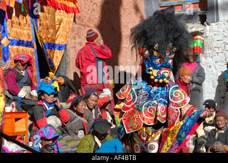 Monk wears fearful and blue mask and dress of a demon amongst many Tibetan pilgrims at festival in colourful - Stock Photo