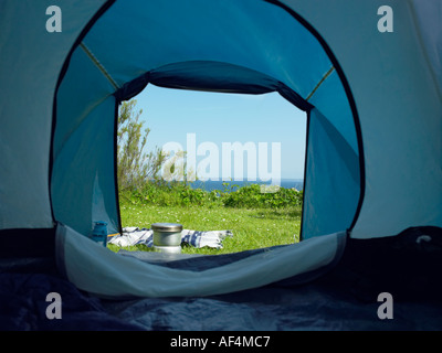 View through tent opening on to green field - Stock Photo