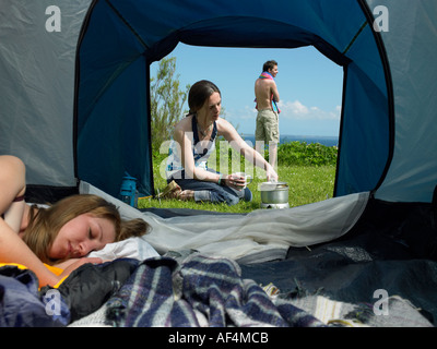 View through tent opening with young female inside whilst another cooks outside with a young male standing - Stock Photo