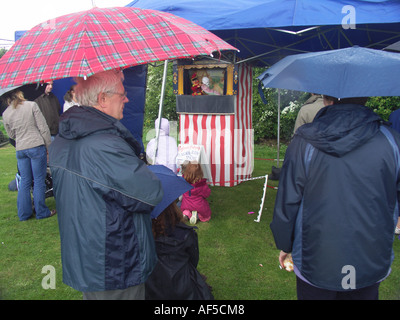 People watching watching a traditional Punch and Judy show at a village fete Suffolk England - Stock Photo