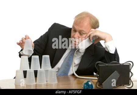 Bored executive playing with cups while on the phone - Stock Photo