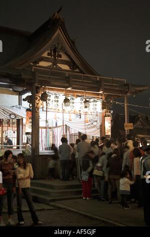 crowds queue up to pray at a small summer festival aomori city namidate street brightly lit shrine nightime night - Stock Photo