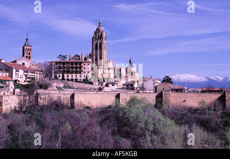 Segovia Cathedral the town walls and the snow capped mountains of Sierra de Guadarrama in the background - Stock Photo