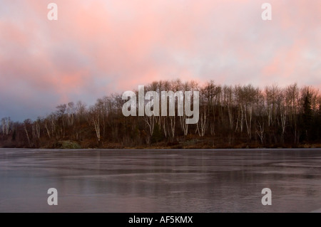 Reflections in ice of St. Pothier Lake at sunrise, Greater Sudbury, Ontario, Canada - Stock Photo