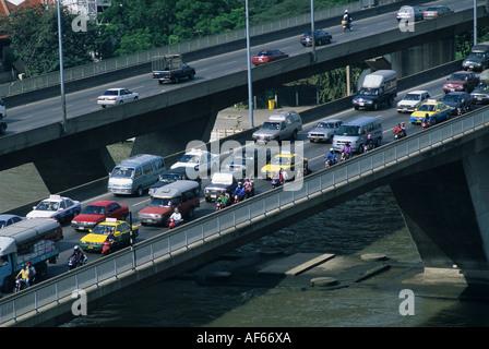 Rush hour traffic jam over the Chao Phraya River bridge in central Bangkok Thailand - Stock Photo