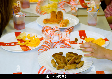 Horizontal close up of savoury party food laid out on a table at a child's ninth birthday party. - Stock Photo