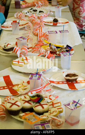 Vertical close up of cakes and biscuit party food laid out on a table at a child's 9th birthday party. - Stock Photo