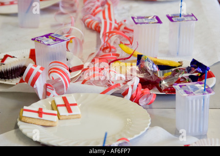 Horizontal close up of food leftovers and rubbish left on a table at a 9th birthday party. - Stock Photo