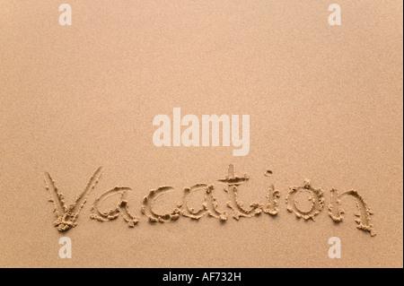 Vacation handwritten in sand plenty of copy space - Stock Photo