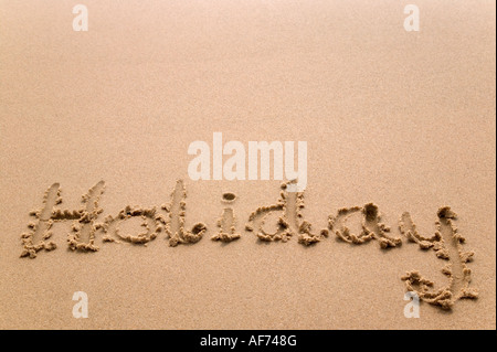 Holiday handwritten in golden sand plenty of copy space - Stock Photo