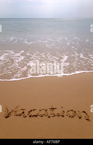 Vacation written in sand on the beach - Stock Photo