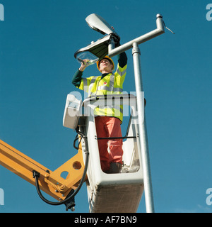 Man standing on cherry picker elevated work platform, maintaining a street light. - Stock Photo
