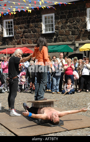 performer lying on a bed of nails with a member of the audience standing on his chest Lughnasa Fair Carrickfergus - Stock Photo