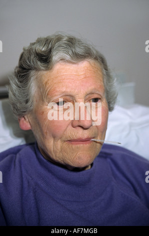 elderly woman having her temperature taken with a disposable thermometer - Stock Photo