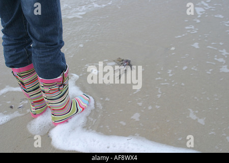 A Stock Photograph of a Woman Running in Wellies along a beach in Scotland - Stock Photo
