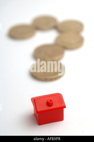 Monolopy house and coins in the shape of a question mark to illustrate house price and interest rate changes - Stock Photo