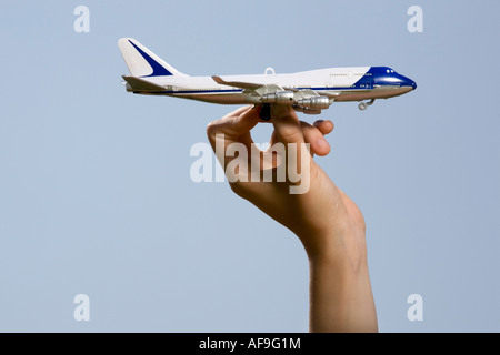 Hand holding toy airplane - Stock Photo