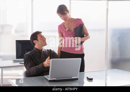Business woman and man working on laptop, teamwork - Stock Photo