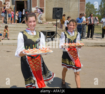 Two young girls in traditional Ukrainian costumes serving canapes in Plotzk / Ukraine - Stock Photo