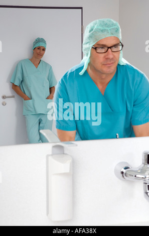 Surgeon washing his hands, female surgeon in background - Stock Photo