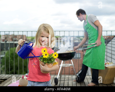 Girl watering flowers, father in background - Stock Photo