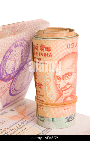 Roll of Indian Rupees on a British Passport with an Indian Visa. Isolated on White. - Stock Photo