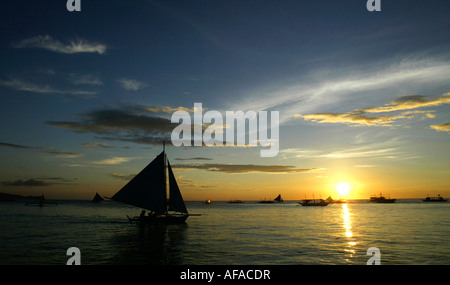 Sailboats off of White beach at sunset in Boracay, Philippines. - Stock Photo