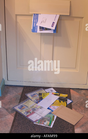 post coming through a letterbox of a house front door and lying on the mat - Stock Photo