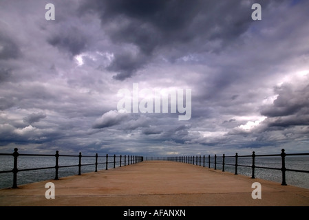 Storm clouds forming over an empty pier - Stock Photo