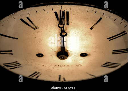 Antique clock face with the hands at 12 o clock dark and grainy sepia toned image - Stock Photo