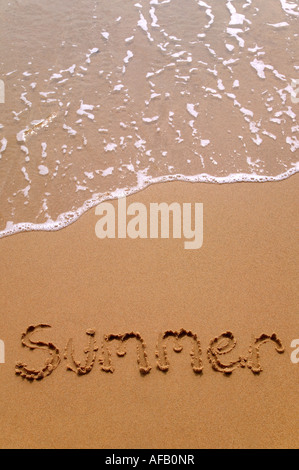Summer written in sand at the beach - Stock Photo