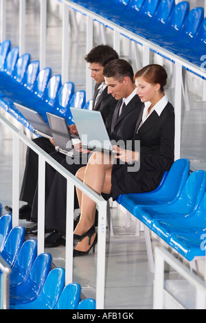 Business people sitting on tribune, using laptop - Stock Photo