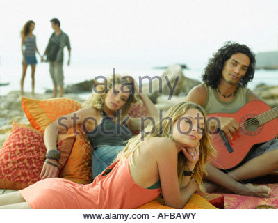 Side profile of a young woman lying in front of a young couple - Stock Photo