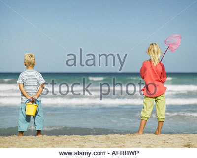 A girl and a boy standing on the beach - Stock Photo