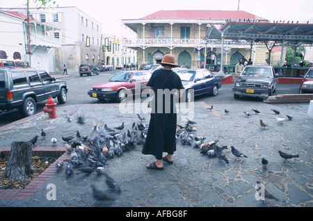 Local woman feeds the pigeons at the Market Square in older part of the capitol of St Charlotte Amalie U Virgin - Stock Photo
