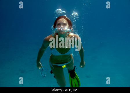 Young woman in bikini blowing bubbles underwater as she fins towards the surface, Cozumel, Quintana Roo, Mexico - Stock Photo